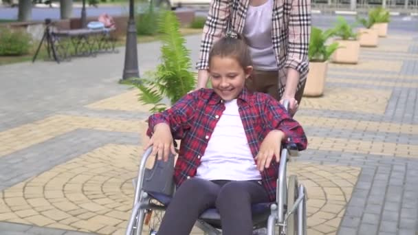 Girl rides happy teen in wheelchair in summer Park.Slow mo