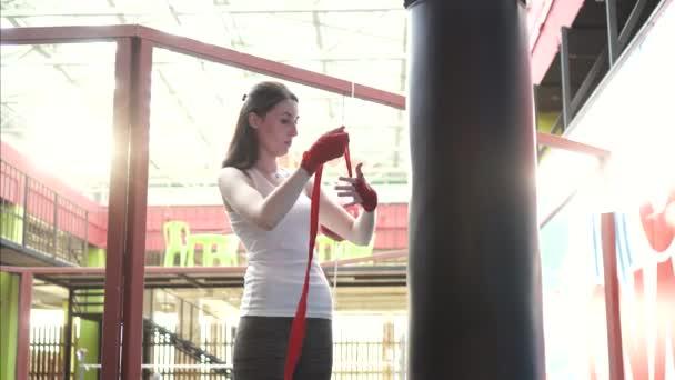Frau wickelt ihre Hände bei Sonnenuntergang in einem modischen Fitnessstudio mit einem Klebeband ein