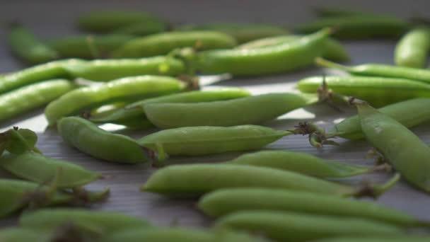 Schoten frischer grüner Erbsen auf dem Tisch