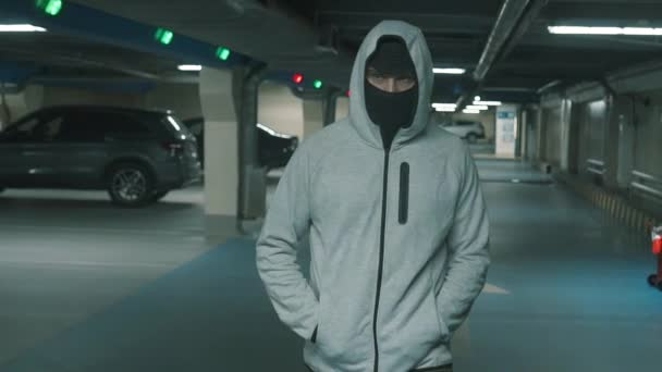 Man criminal in black balaclava and hood walks and looks around menacingly.Slow mo