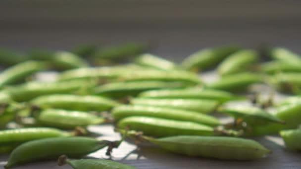 Schoten frischer grüner Erbsen auf dem Tisch.slow mo