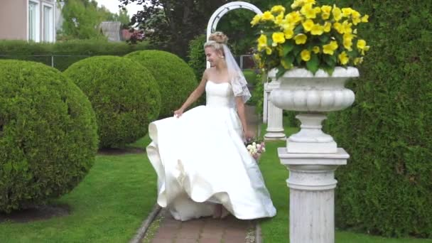 the bride in a white dress,spinning in slow motion in a beautiful garden