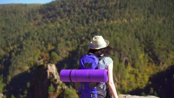 Turistické dívka s batohem na zádech s otevřenou náručí na vrcholu hory