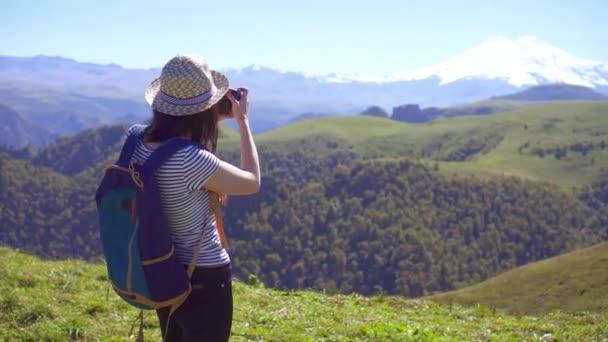 Rückansicht des Mädchens mit Rucksack auf den Rücken und Fotografieren mit Digitalkamera