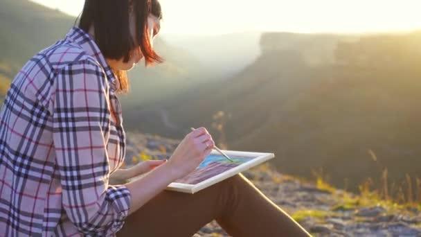 Dívka umělec maluje obraz hor a západ slunce