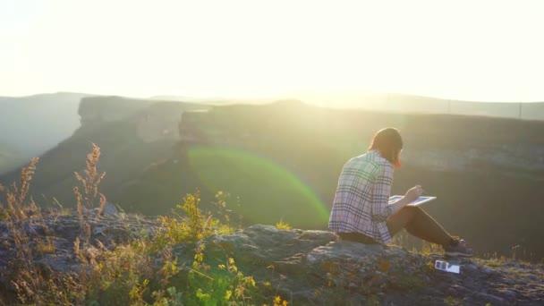 Dívka umělec maluje krajiny hor a západ slunce, sluneční záře