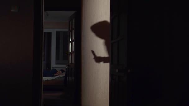 Stín na zdi maskovaný lupič s nožem v ruce