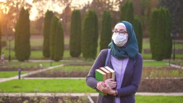 Muslimských studentů s knihami v hidžábu s batohem a lékařské ochranný obvaz na její tvář v parku