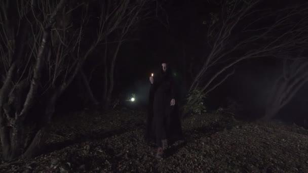 mystické dívka v temném lese se svíčkou v tmavém plášti