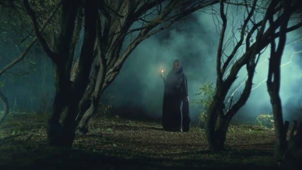 misztikus lány egy sötét erdőben egy gyertyát