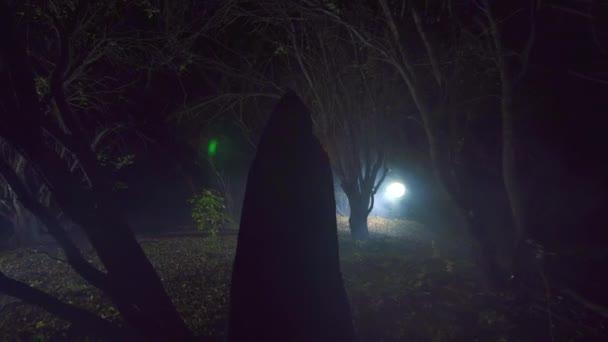 postava v černém hávu se svíčkou prochází tajemný les