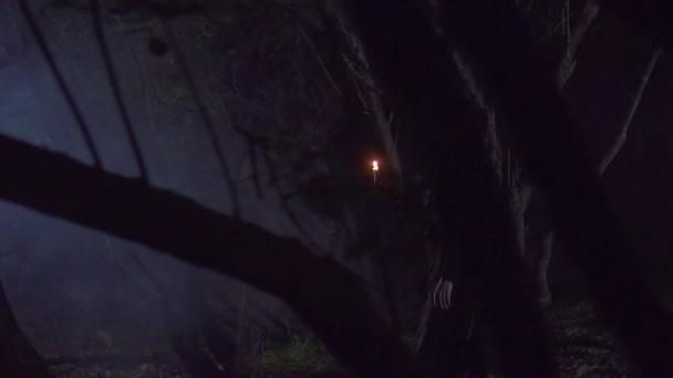 misztikus lány, egy gyertya, séta a sötét erdőben, lassú mo