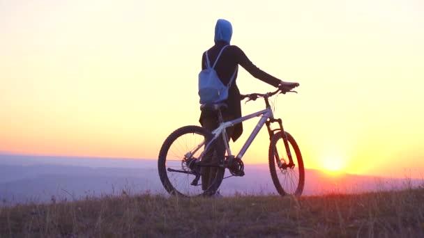 Muslimské ženy v hidžábu s batohem s kolo z hory se dívá na západ slunce, pomalé mo
