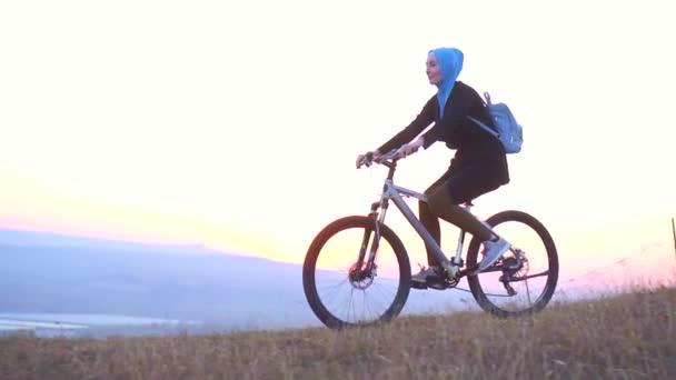 Muslimské ženy v hidžábu s batohem jezdí na kole z hory v západu slunce, pomalé mo