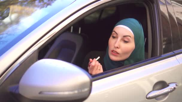 Muslim woman in a hijab sits in a car and paints her lips with lipstick