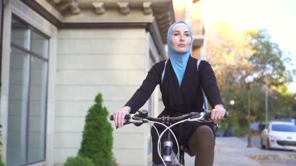 Portrét mladé muslimské ženy v hidžábu na kole ve městě, pomalé mo
