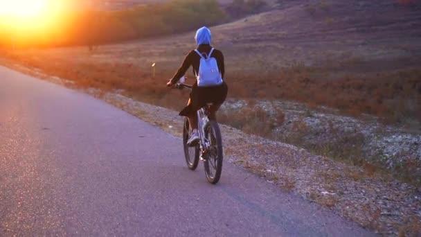 Muslimské ženy v hidžábu s batohem, jízda na kole na silnici zapadajícího slunce, zadní pohled, pomalé mo