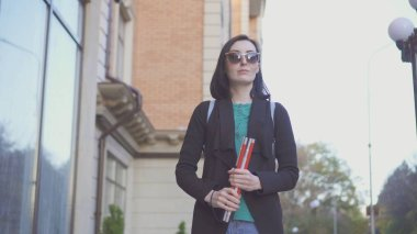 portrait of a blind girl in glasses with a cane on a city street