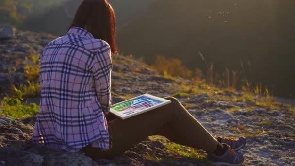 Dívka umělec kreslí maluje krajinu pohoří