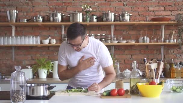 Szemüveges fiatalember darabolt zöldségeket, a konyhában, és a tapasztalatok egy éles szívfájdalom