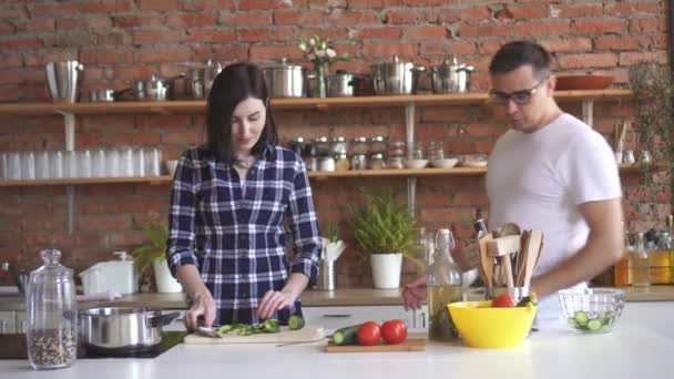 Portrait of a young couple in the kitchen,girl cuts vegetables and gives a man a try