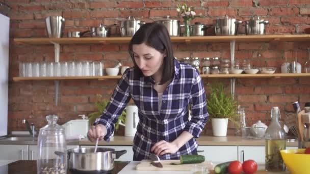 Žena hospodyně v kuchyni kusy zeleniny a vaří večeři, na kamna přidávání koření do pánve