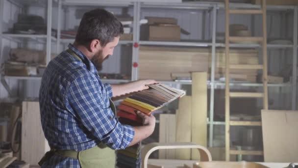 brutální muž v vousy Kraftman vybere barevnou paletu tkaniny pro výrobu nábytku