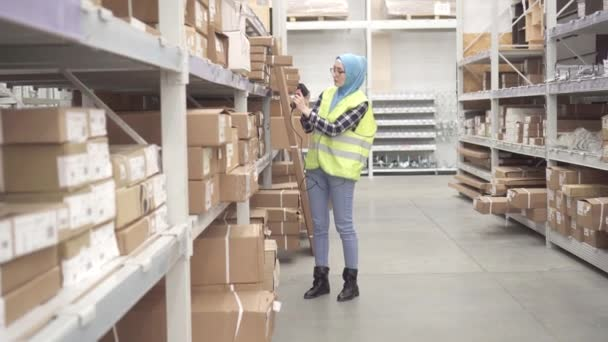 Muslim in a hijab holds inventory with barcode scanner