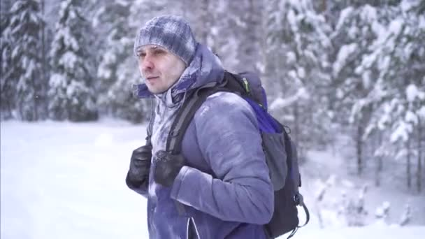 frozen man tourist in the snow, goes through the woods with a backpack