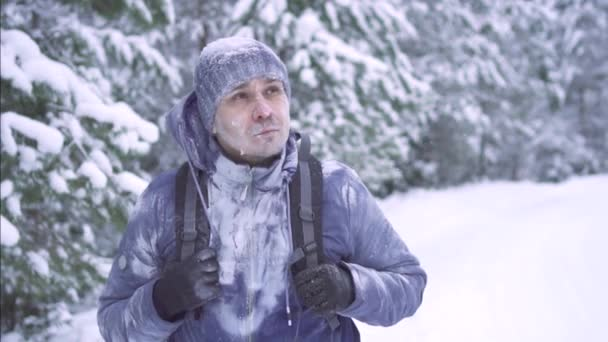 frozen man in the snow, walking through the woods with a backpack