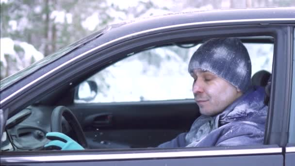 portrait cheerful frozen man sits in the car and shows thumb up