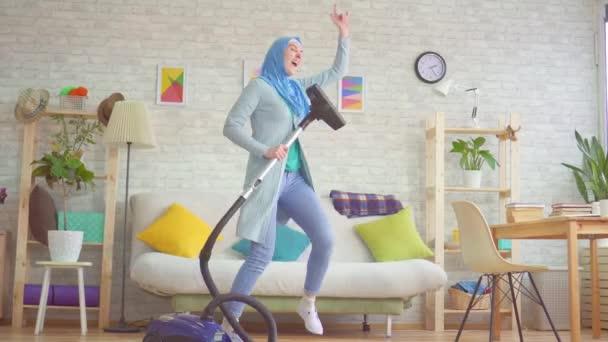 Muslimische Frau im Hidschab saugt Teppich und tanzt und singt