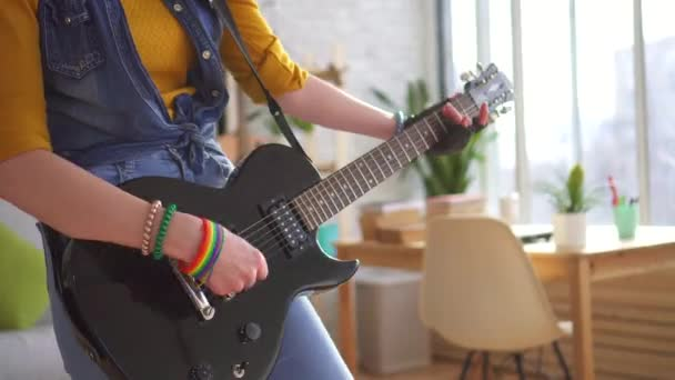 Close up of young woman rocker playing electric guitar in modern apartment