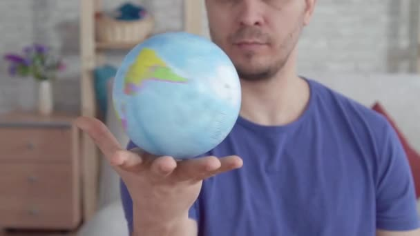 Close up globe spinning in the palm of a man slow mo