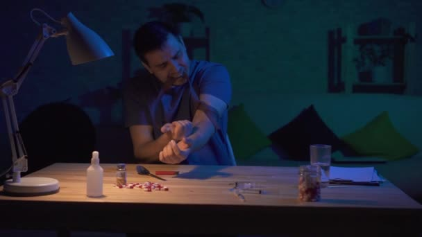 Man drug addict in a dark room at the table doing an injection