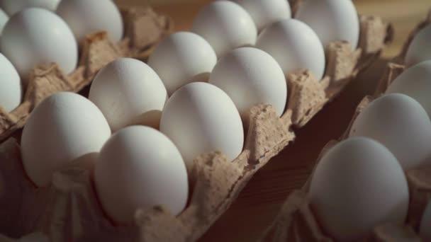 Közelíti meg a csirke tojás egy kartondobozban az asztalra.