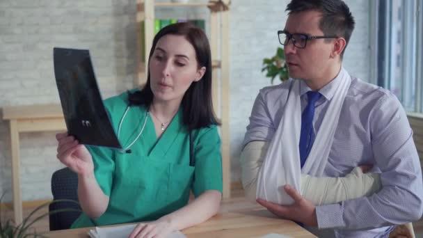 Žena lékař s rentgenem v ruce komunikuje s pacientem se zlomenou rukou