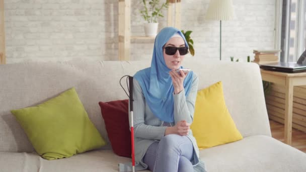 beautiful blind Muslim girl in hijab at home,enjoys smartphone