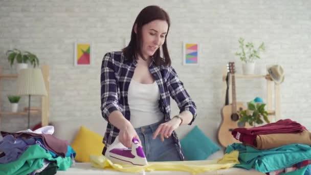 fröhliche junge Frau im karierten Hemd gebügeltes Leinenbügeleisen zu Hause, tanzend