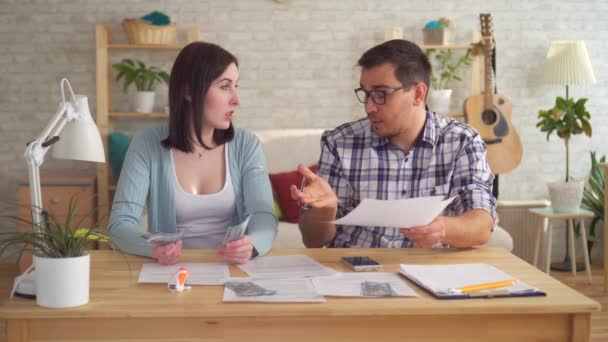 Young couple concerned and tense, doing the calculations documents with calculator