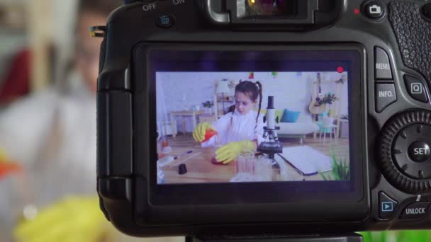 camera screen girl teen blogger youtuber in a white coat and goggles in lab ,homework microscope