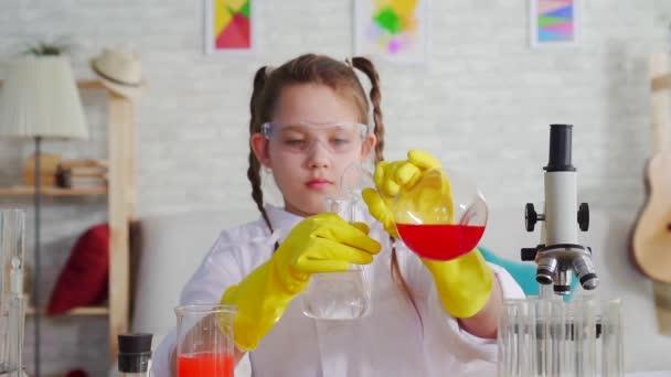 ragazza teen blogger in un camice bianco e occhiali in laboratorio ,mescola i reagenti