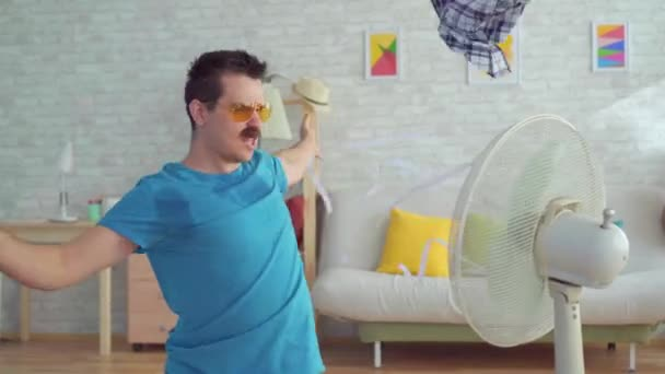 Funny young man with electric fan enjoying cool wind in his apartment