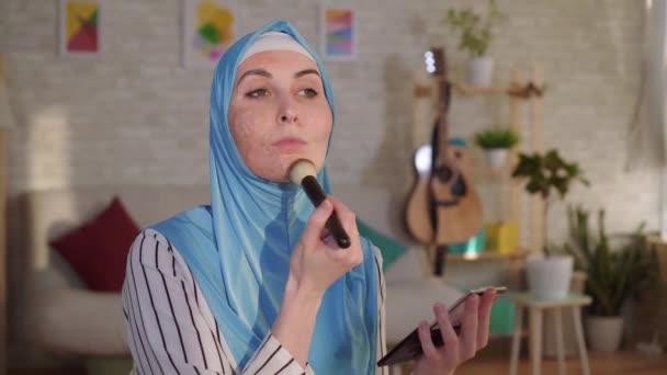 Muslimische Frau im Hijab mit Brandnarbe im Gesicht beim Make-up