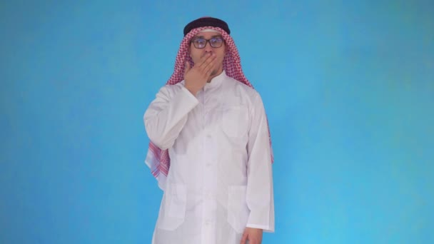Surprised Arab man stands on blue background