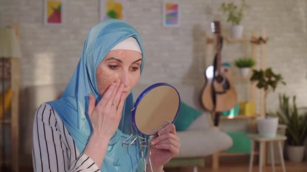 Muslim woman in a hijab looks in the mirror at her scar from a burn on her face