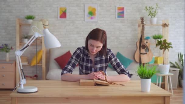 junge Frau sitzt an einem Tisch mit einem Rosenkranz in der Hand und liest ein Buch