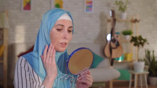 Muslim woman in a hijab looks in the mirror at her scar from a burn on her face and cries