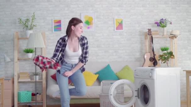 fröhliche junge Hausfrau wäscht Kleider und tanzt in moderner Wohnung