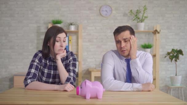 Manželé sedí doma u stolu a vypadají zmateně na prasátko